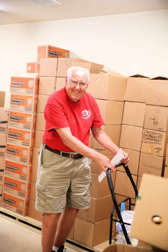 An ECHO volunteer pushes a dolly full of supplies.
